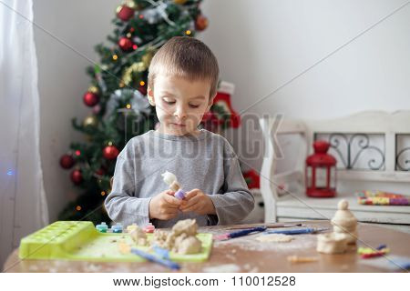 Cute little boy, playing with modeling dough, molding figures at home on Christmas