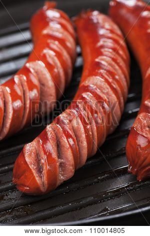Grilled german sausages in grilling pan, close up image