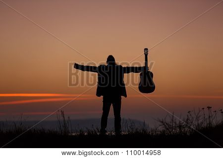 Man standing with guitar in sunset time poster