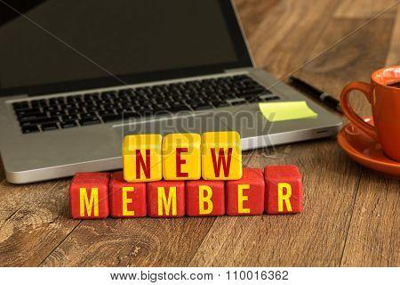 New Member written on a wooden cube in a office desk