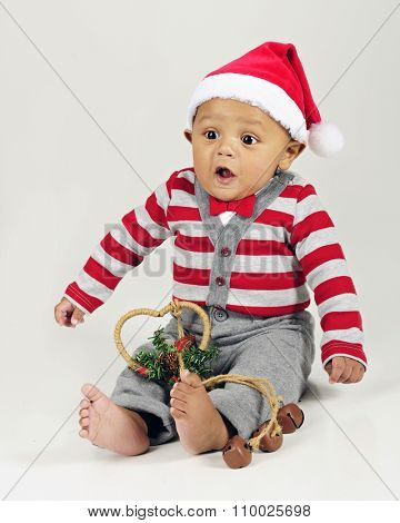 An adorable baby boy looking surprised as he sits in his Santa Hat and bow tie with  a heart-shaped ornament with with jingle bells on his lap.  On a gray background.
