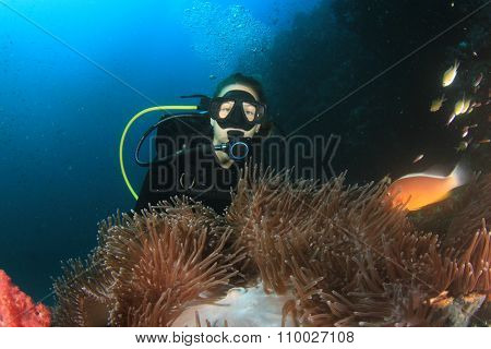 Young Woman Scuba diver finds Nemo: Anemonefish clownfish on underwater coral reef