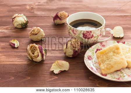 Rosebuds And A Mug Of Coffee And Cake On A Dark Wooden Background