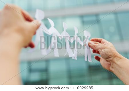 Two hands holding a business team made of paper cut-outs
