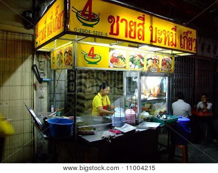 Thai woman cooks and sells Thai noodles.