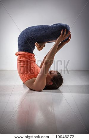 Sporty fit yogini woman practices inverted yoga asana Urdhva padmasana - lifted lotus pose
