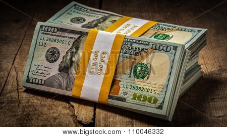 Creative business finance making money concept - panorama of stacks of new 100 US dollars 2013 edition banknotes (bills) bundles isolated on wooden background