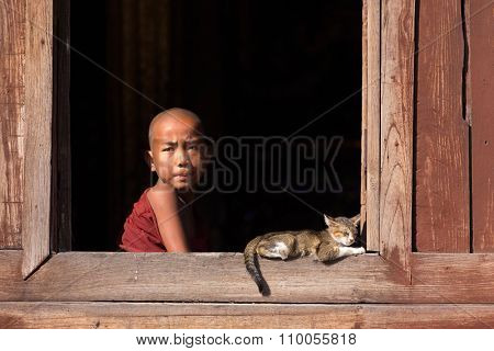 NYAUNG SHWE, MYANMAR, JANUARY 27, 2015 : A young novice buddhist monk is looking at the window of the Shwe Yaunghwe Kyaung monastery in Nyaung Shwe, Myanmar (Burma).