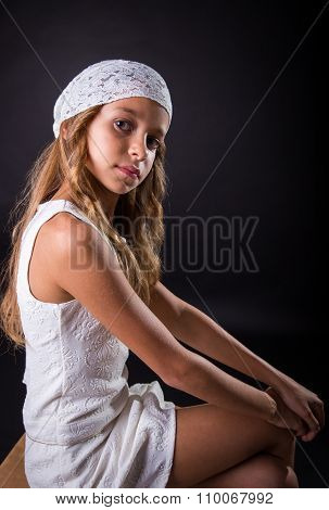 Young Girl With White Cap And Sober Look Sitting On Black Background