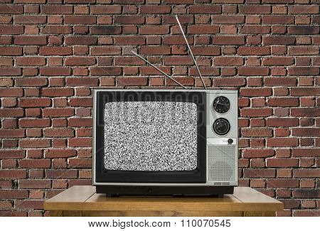 Old analogue television with static screen and brick wall.