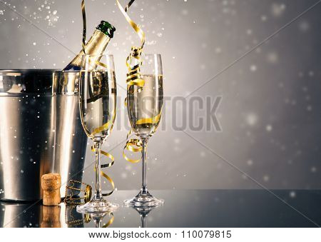 Pair glass of champagne with bottle in metal container. New Year celebration theme with blur spots of bubbles