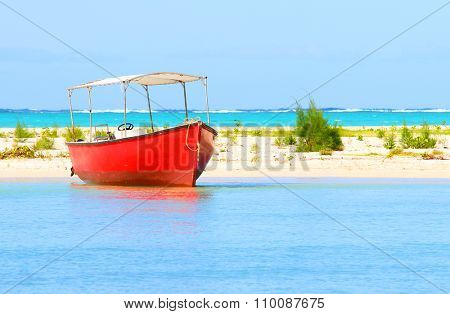 Red motor boat on Indian Ocean near Ile Aux Cerfs Island ( Mauritius Island). Blue sea and beach in tropical paradise.