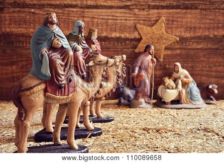 the three kings on their camels and the holy family in a rustic nativity scene