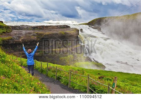 On mountain slope the woman delighted looks at a boiling chasm. Powerful Gullfoss in Iceland.