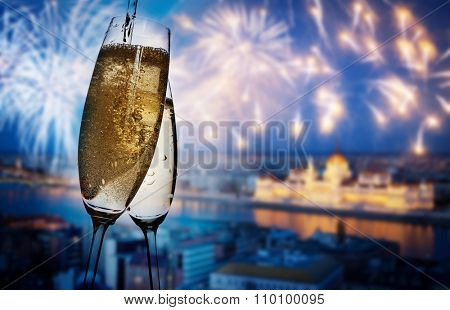 New Year in Budapest - Champagne glasses and Budapest parliament with fireworks in the background