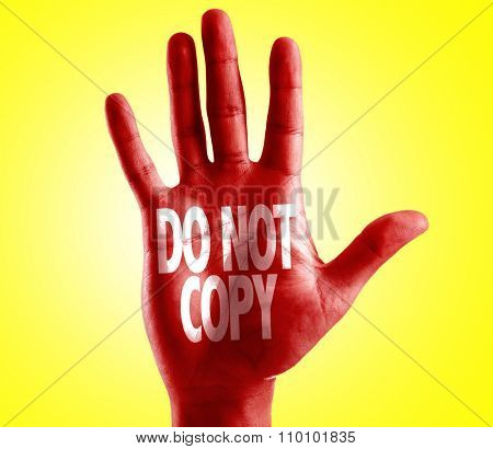Do Not Copy written on hand with yellow background
