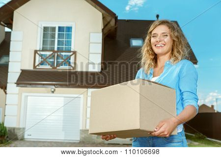 Woman carrying boxes in to new house