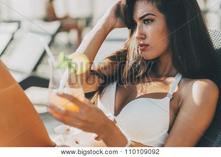 Seductive young woman drinking cocktail and sunbathing poster