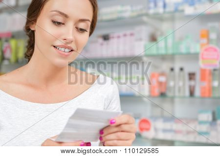 Beautiful girl reading instructions to the medicine