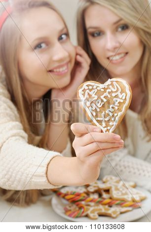 Close Up Of Christmas Heart Shape Home Cookies In Girl's Hand On Happy Smiling Young Girls Backgroun
