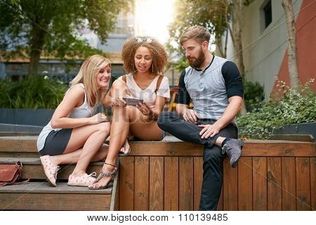 Young Friends Outdoors Using Mobile Phone