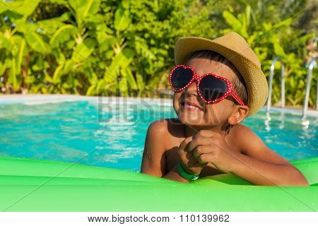 Cute boy on green air bed in the swimming pool