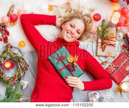 Happy woman lying on the floor with gift box in hand