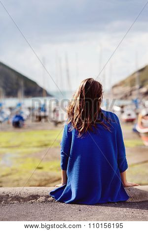 Young Woman, Sitting On A Harbor, Looking At The Ocean