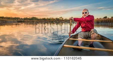 senior paddler enjoying paddling a canoe on a calm lake at sunset, Riverbend Ponds Natural Area, Fort Collins, Colorado