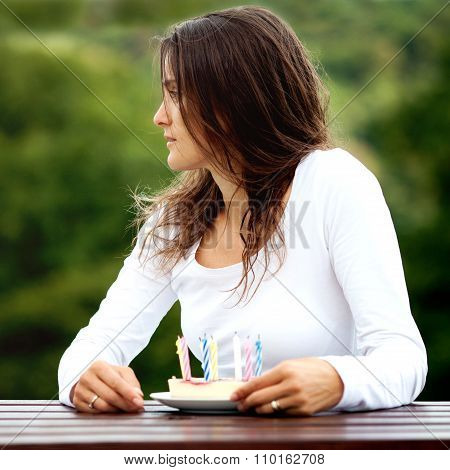 Stylish Girl With Cake And Candles Sitting On Bench
