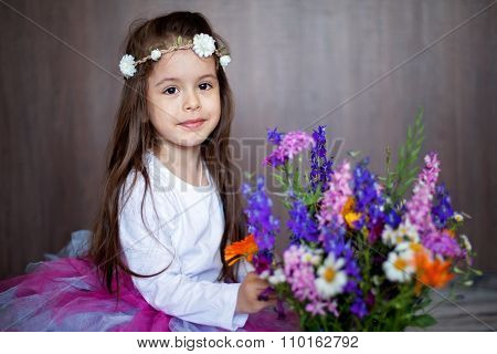 Close Portrait Of A Little Sweet Smiling Girl Holding Bouquet Of Flowers, Wearing Tutu Skirt And Hea