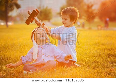 Two Boys, Playing With Airplane On Sunset In The Park