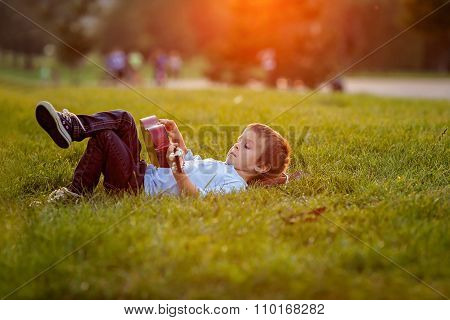 Adorable Boy With Guitar, Sitting On The Grass