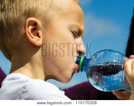 Little thirsty boy child drink water from plastic bottle outdoor poster