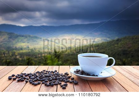 White Coffee Cup And Coffee Beans On Wood Table And View Of Sunset Or Sunrise Background