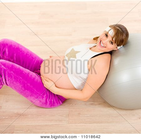 Smiling beautiful pregnant woman sitting on floor and relaxing after exercising