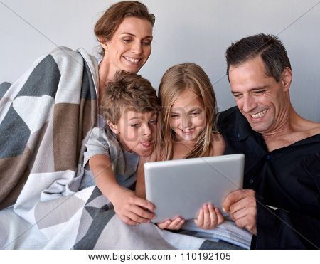 Happy caucasian family with two kids spending quality time internet video call on tablet device at home