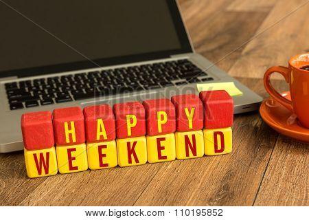Happy Weekend written on a wooden cube in a office desk