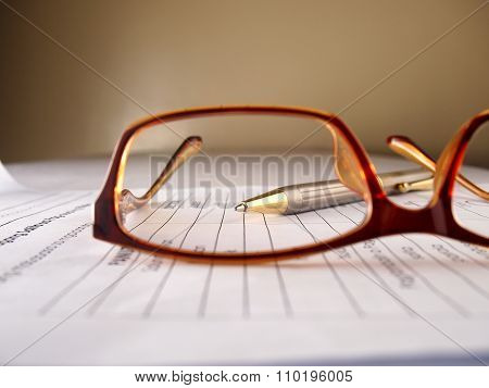 Eyeglasses, pen and paper
