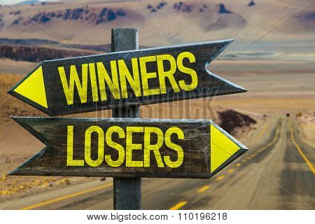 Winners - Losers signpost in a desert road on background
