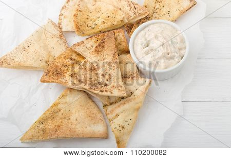 homemade pita chips on white paper with yogurt sauce