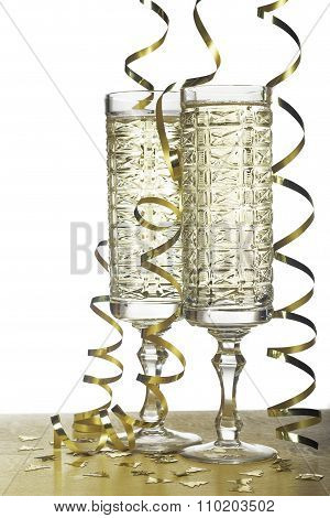 Flutes Of Champagne And Streamer On Holidays. Isolated On White .