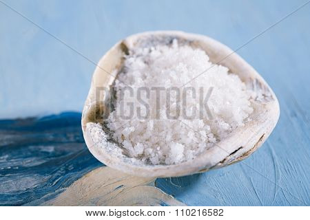 Fleur de sel sea salt in oyster sea shell  on blue abstract painted background