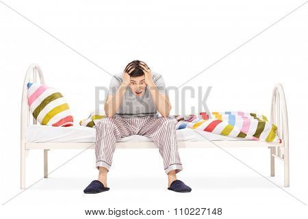 Young guy in pajamas sitting on a bed and suffering from insomnia isolated on white background