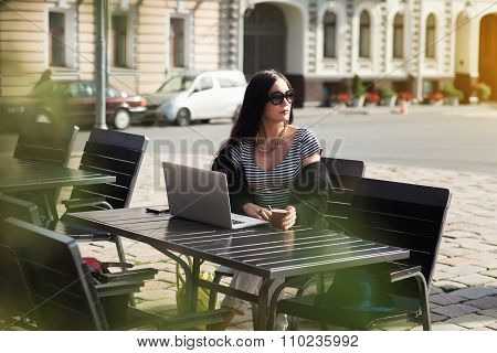 Fashionable brunette woman sitting with laptop computer in sidewalk cafe in sunny autumn day