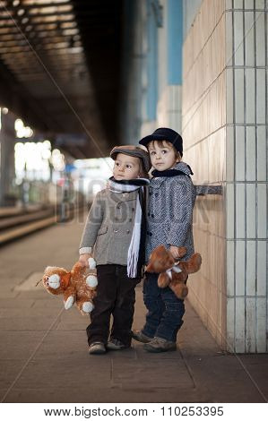 Two Little Boys With Their Teddy Bears On The Mail Railway Station In Prague