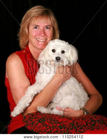 A classic portrait of a Beautiful Blonde Woman with her Beautiful White Pure Breed Bichon - Maltese Dog. Shot in studio against black velvet with studio lights and a red and green blanket.