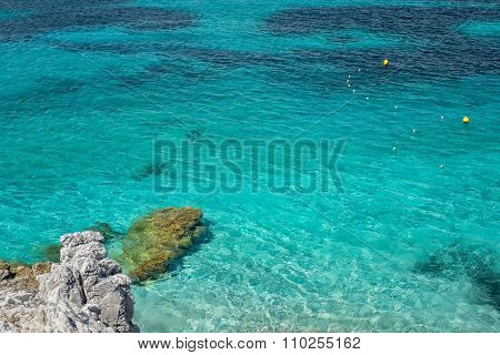 Clear Turquoise Sea Water And Stones. Greece.