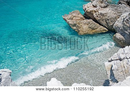 Clear Turquoise Sea Water, Stones And Wave. Greece.