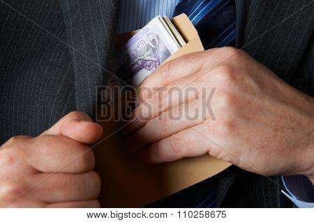 Businessman Putting Envelope Filled With Sterling In Jacket Pock